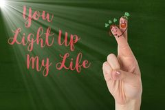 Fingers with smiley face and love message. Digitally generated image of fingers with smiley face and love message against green background Stock Photo
