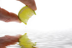 Fingers squeezing lemon. A closeup view of two fingers squeezing a juicy lemon slice over rippled water Royalty Free Stock Images