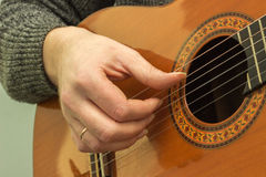 The fingers on the strings of a guitar playing Stock Photos
