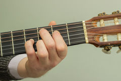 The fingers on the strings of a guitar playing. The fingers on the strings played with wooden guitar Royalty Free Stock Photography