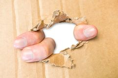 Fingers tear hole in cardboard paper Royalty Free Stock Photography