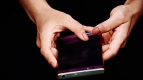 The fingers are texting on mobile phones in the hands of women stock video footage