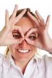 Fingers to circles around eyes Stock Photo