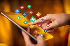 Fingers touching tablet with apps. Female hands touching tablet with colorful applications Stock Photos