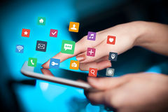 Fingers touching tablet with apps. Female hands touching tablet with colorful applications Royalty Free Stock Images