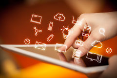 Fingers touching tablet with icons. Female hands touching tablet with white technology related icons Stock Photography