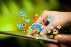 Fingers touching tablet with social icons. Female hands touching tablet with colorful social media icons Royalty Free Stock Image
