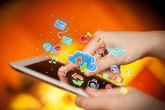 Fingers touching tablet with social icons. Female hands touching tablet with colorful social media icons Stock Photography