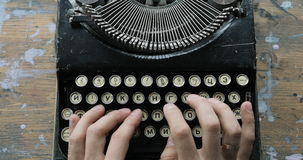 Fingers typing on the keyboard of an old-fashioned typewriter, view from above. Fingers typing on the keyboard of an old-fashioned typewriter stock video footage