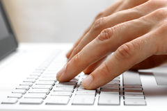 Fingers typing on laptop computer keyboard. Fingers typing on white laptop computer keyboard Royalty Free Stock Photography