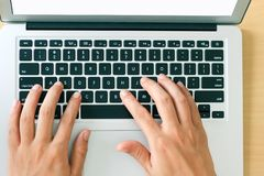 Fingers typing on laptop keys, closeup top view stock image