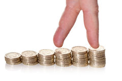 Fingers walking up on stacks of one pound coins. On white background. Way to economical growth concept Stock Image
