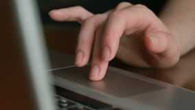 Fingers working on a laptop touchpad, close-up stock video footage