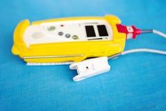 Fingertip Pulse Oximeter for oxyhemoglobin. On blue background royalty free stock photography
