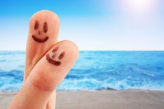 Fingertips with smiley faces at the beach Stock Images