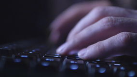 FingFingers typing on keyboard at night. Male hands working at computer late. Close upers typing on keyboard at night stock footage