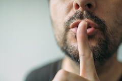 Fingra på kanter, mannen som gör en gest shhh tecknet Fotografering för Bildbyråer