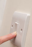 Fingra roterande PÅ den ljusa strömbrytaren på väggKOPIERINGSUTRYMME Royaltyfri Foto