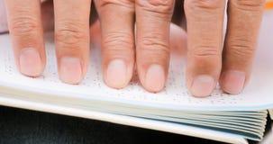 Fingrar av den rörande sidan för blind man på blindskriftboken Royaltyfri Fotografi
