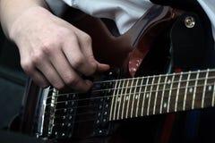 Fingrar av en ung gitarrist på de bas- raderna av en elektrisk gitarr musikaliskt tema Närbild fotografering för bildbyråer