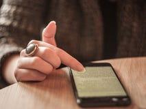 Fingrar av en ung vit caucasian kvinna som bläddrar en smartphone med internet som 3G mycket visar en bred skärm av text Arkivbild