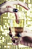 Fingrar det nära övre fotoet för skönhet med hållande exponeringsglas för manikyr av champagne Royaltyfria Bilder