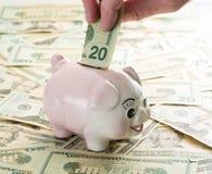 Räcka att förlägga 20 dollar räkning in i piggy packar ihop Arkivfoton