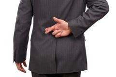 Fingrar korsade bak businessmans baksidt Fotografering för Bildbyråer