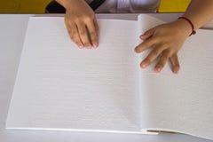 Fingrar och braille. det blinda folket läste en boka i braille. Royaltyfri Foto