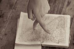 Fingrar som marscherar på översikten i en gammal bok arkivbild