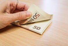 Fingrar som räknar en bunt av pengar royaltyfria foton