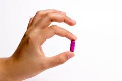 Fingrar som rymmer en preventivpiller Arkivfoto