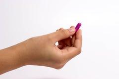 Fingrar som rymmer en preventivpiller Royaltyfri Foto