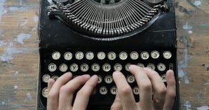 Fingrar som skriver på tangentbordet av en gammalmodig skrivmaskin, sikt från över lager videofilmer
