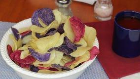 Fingrar som väljer färgrika potatischiper stock video