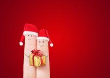 Fingrar vänder mot i jultomtenhattar med gåvaasken på mörker - röd bakgrund Arkivbild