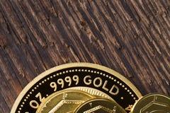 Finhet 999 för några guld- mynt 9 på en bakgrund av grov trätextur royaltyfria foton