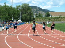 Finish of the 100 meters dash. KELOWNA, CANADA - Kong Tim, Meng Zhayate, Elke Daniel, Amos Zachary, Hartling Dylan, Wang Jason, finale Men 16-17 100 Meter Dash Royalty Free Stock Photo