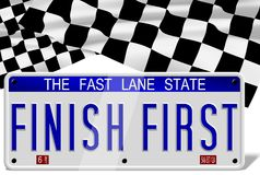 Finish first number plates. White number plates spelling finish first and a finish flag in the background Royalty Free Stock Images