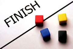 Finish Line. Several game tokens, one has crossed the finish line royalty free stock photo