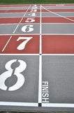 Finish line. With numbers on red tartan athletic tracks Stock Images