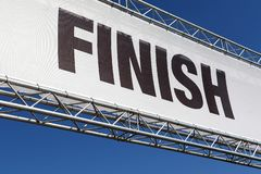 A finish line banner isolated across a clear blue sky. A finish line banner in a metal framework isolated across a clear blue sky stock images