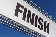 A finish line banner isolated across a clear blue sky. A finish line banner in a metal framework isolated across a clear blue sky stock image