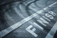 Finish line painted on the floor. Finish line painted on the asphalt ground with crossing of tires tracks royalty free stock photography