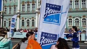 The finish line of the St. Petersburg marathon. Spectators, cheerleader, flag sponsor Zenith and runners