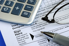Finish and sign the income tax return. Isolated on blue Stock Images