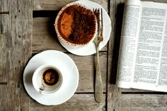 Finished breakfast with coffee and chocolate muffin and book Royalty Free Stock Photo