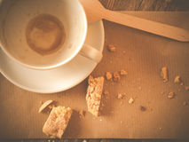 Finished coffee break. Photo shows the topview of a finished coffee break showing an empty and dirty coffee cup,  crumps and bited biscotti; wooden background Royalty Free Stock Images