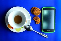 Finished Coffee in a ceramic cup, cookies and a cellphone Stock Photo