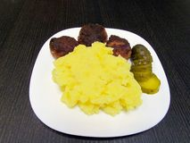 The finished dish which consists of patties, mashed potatoes and pickled cucumbers stock photos